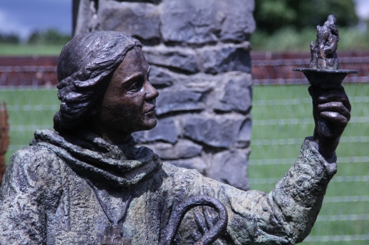 Statue of St. Brigid with braided hair wearing robes and a cross necklace. In one hand is a shepherd's staff, in the other a lit torch.